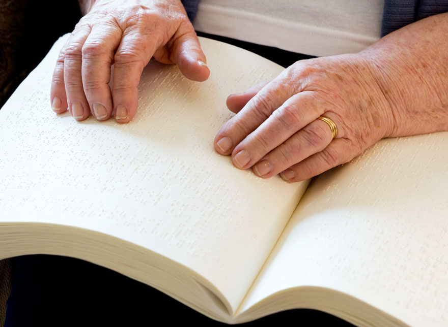 An elderly person's hands reading a Braille book.