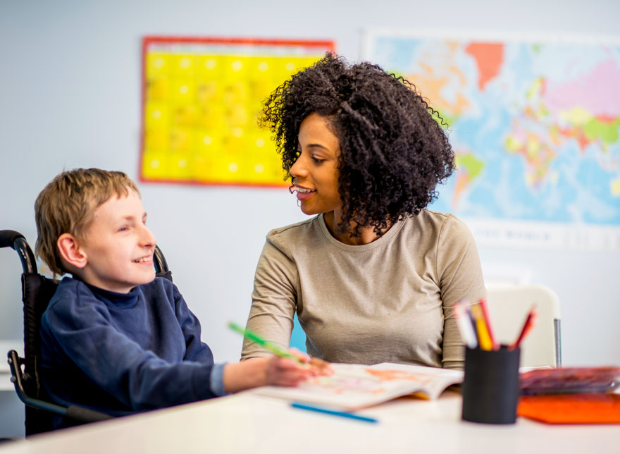 Teacher working with boy.